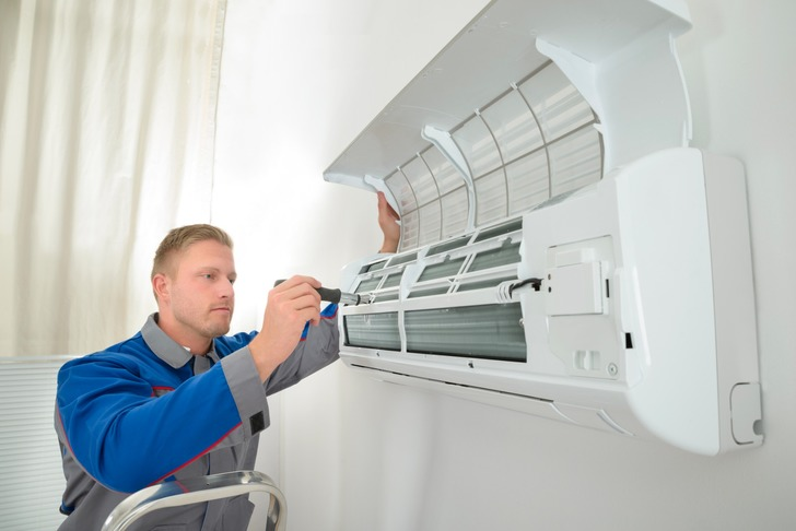 one of our air conditioning maintenance engineers in Hinckley, Leicester, servicing an air conditioning unit